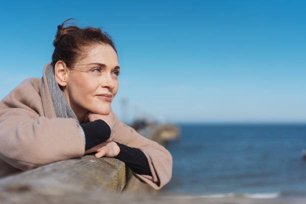Pensive young woman relaxing on a wooden pier Pensive young woman relaxing on a wooden pier enjoying the winter sunshine leaning on the railing staring out over the ocean one mid adult woman only stock pictures, royalty-free photos & images