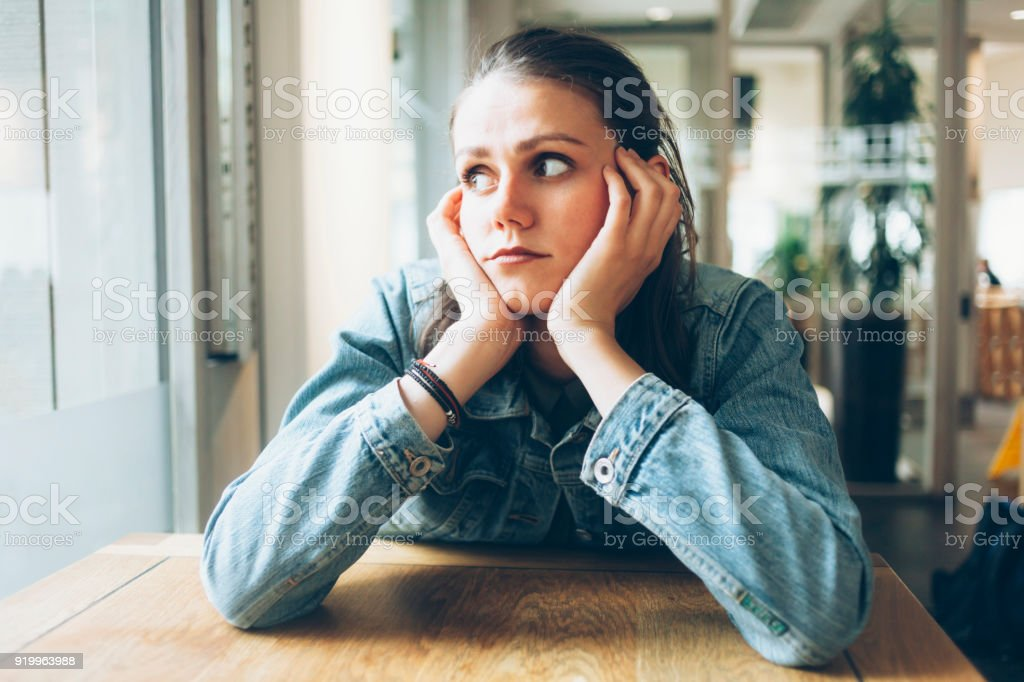 Pensive young woman sitting in cafe alone stock photo