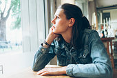 Side view of pensive young woman sitting in cafe, hands on chin. Looking through window.