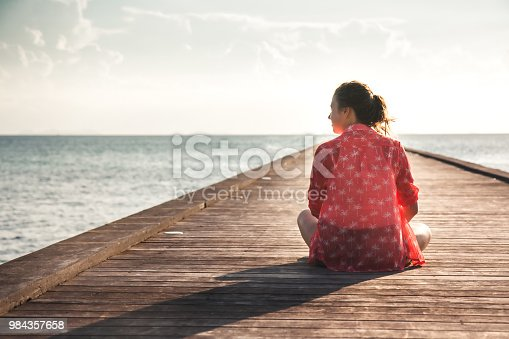Pensive young woman tourist enjoy her life sitting on pier beach with infinity sea view copy space