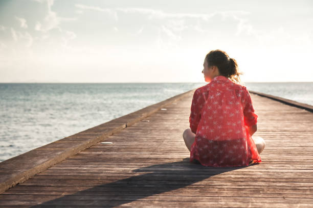 Pensive young woman tourist enjoy her life sitting on pier beach with infinity view copy space Pensive young woman tourist enjoy her life sitting on pier beach with infinity sea view copy space introspection stock pictures, royalty-free photos & images