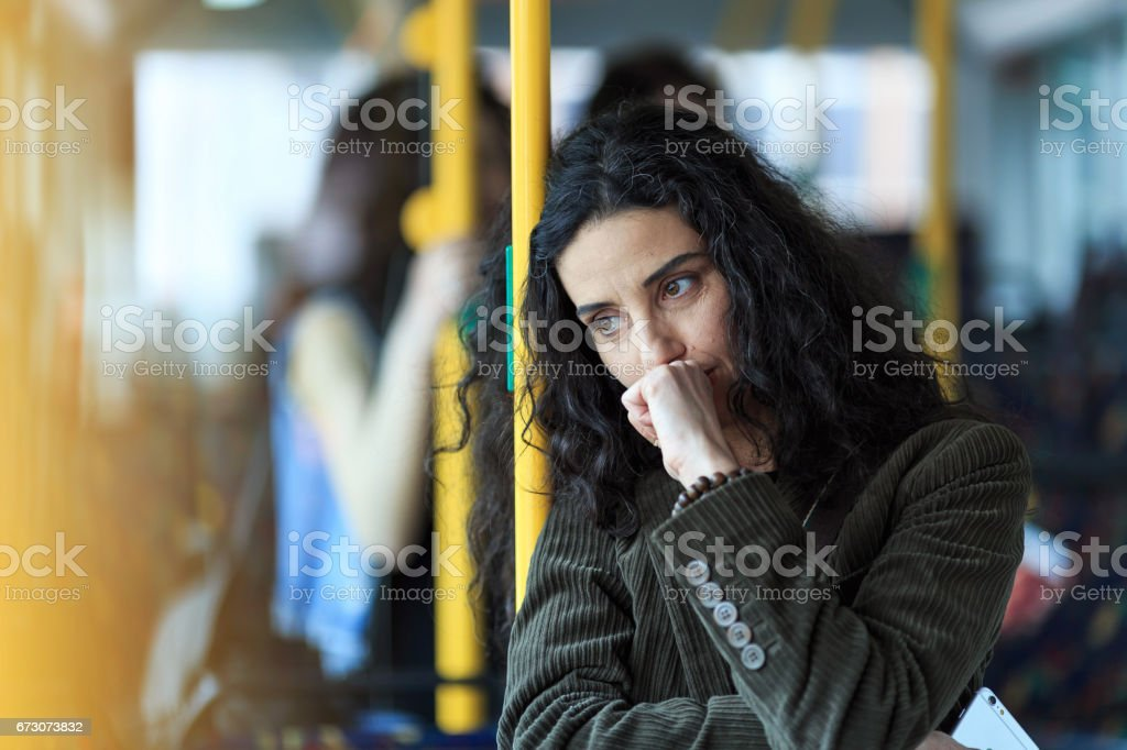 Pensive young woman traveling and holding smart phone stock photo