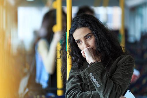 Nachdenkliche Junge Frau Unterwegs Und Halten Smartphone Stockfoto und mehr Bilder von Am Telefon