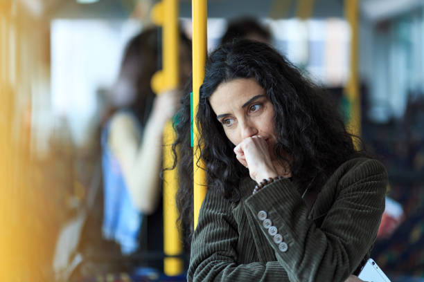 Pensive young woman traveling and holding smart phone Pensive young woman traveling with bus and holding smart phone. Wears casual clothes. apprehension stock pictures, royalty-free photos & images