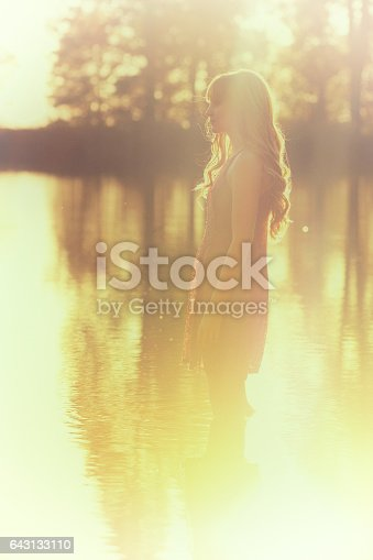 A young woman in a dress wades into a picturesque lake at sunset