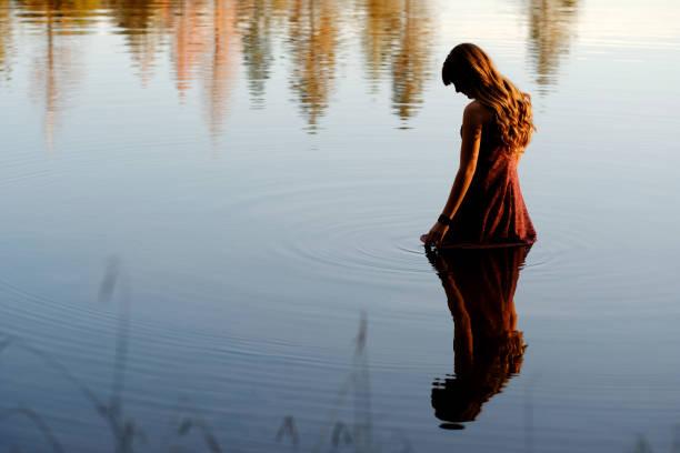 夕暮れ時の湖でウェーディング物思いにふける若い女性 - 水につかる ストックフォトと画像