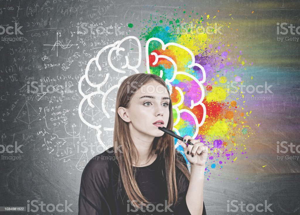 Pensive young woman with pen, brain stock photo