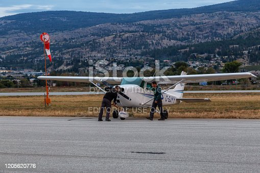 Penticton, British Columbia, Canada - September 24, 2016: Pilot and Co-Pilot parking a small Cessna Airplane on the Apron at Penticton Regional Airport (YYF) during a colorful sunset.
