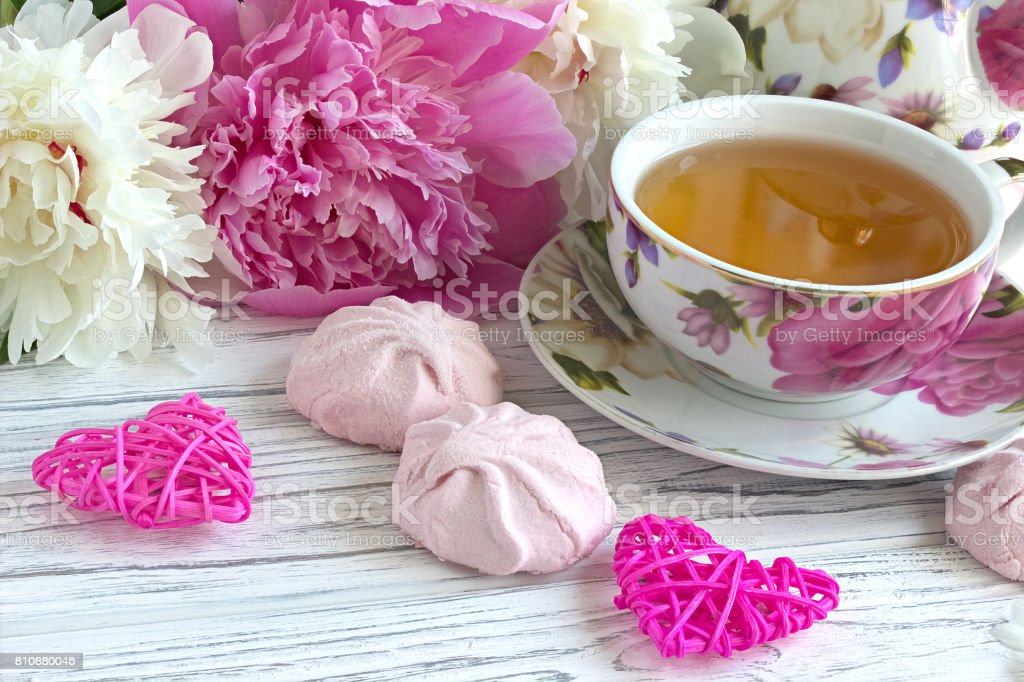peonies-fl​owers-pink​-cup-of-te​a-rattan-h​earts-mars​hmallow-on​-a-white-p​icture-id8​10880046