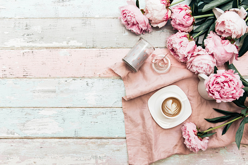 istock Peony flowers and coffee cup on shabby chic background. Top view 972885498
