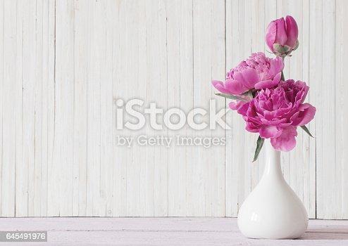 istock Peony flowers in  vase on white background 645491976