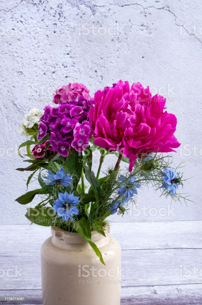 Peony, Nigella and Sweet Williams in a vintage pot. stock photo