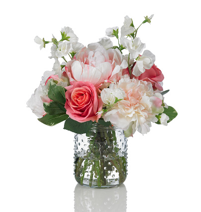 A beautiful springtime arrangement of flowers in a hobnail glass jar. The bouquet contains roses, peonies, and sweet peas. Shot against a bright white background. There is a path which may be used to delete the reflection if desired. Extremely high quality faux flowers.