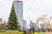 Warsaw, Poland - December 18, 2019: Peopl outside Westfield Arkadia shopping mall with Christmas decorations and tree and modern building sign for multimedia
