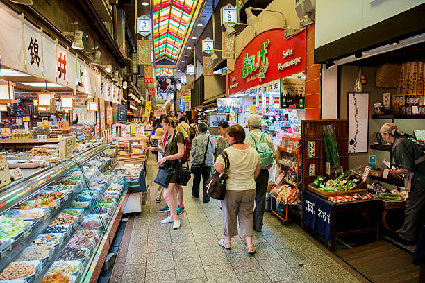 People amidst stalls at Nishiki Market Kyoto, Japan - Jun 17, 2016: Customers at illuminated Nishiki Market. Tourists walking on alley amidst stalls. It is one of the famous place. amidst stock pictures, royalty-free photos & images