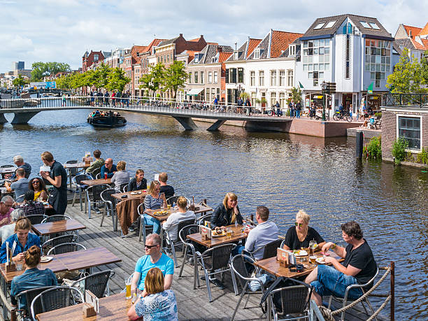 People and bridge over Rhine canal, Leiden, Netherlands Leiden, Netherlands - August 9, 2016: People on outdoor terrace of cafe, bridge and historic gables on quay of Rhine canal in old town of Leiden, South Holland, Netherlands leiden stock pictures, royalty-free photos & images