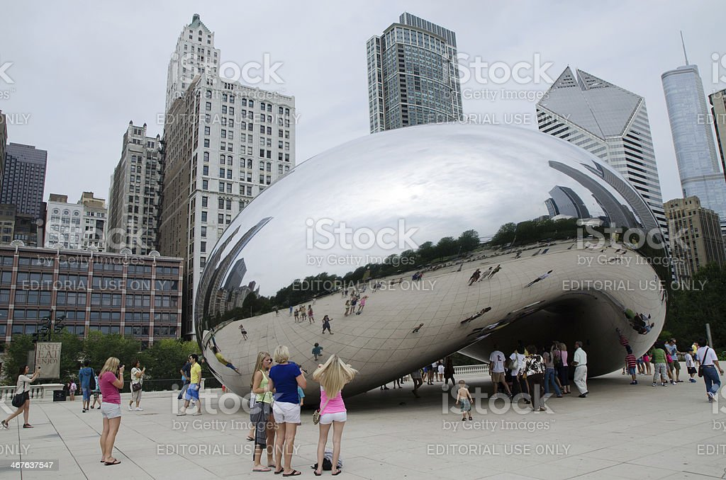 People and buildings reflecting in the famous Chicago Bean stock photo