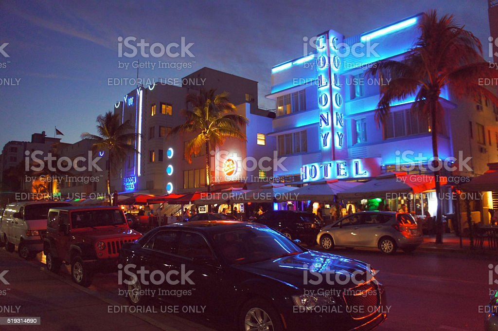 People and cars move alongside the night Ocean Drive street stock photo