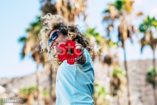 People and happiness concept with young beautiful blonde curly woman jumping in background with red flower on focus - outdoor nature in background for joyful lifesyle