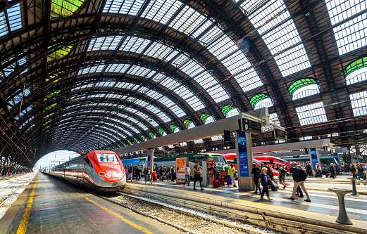People and high-speed trains at the railway Milan Central Station