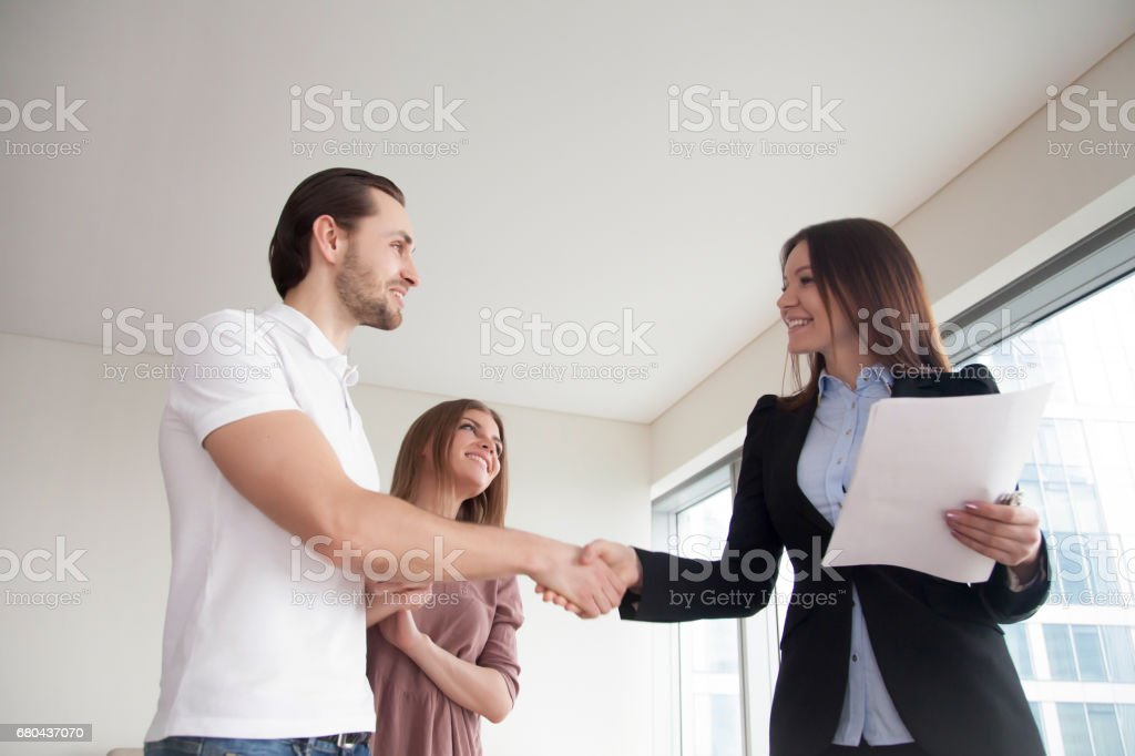 People and real estate. Young couple and female broker handshaking stock photo