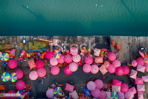 istock People and sun umbrellas on fish market. 1069060338