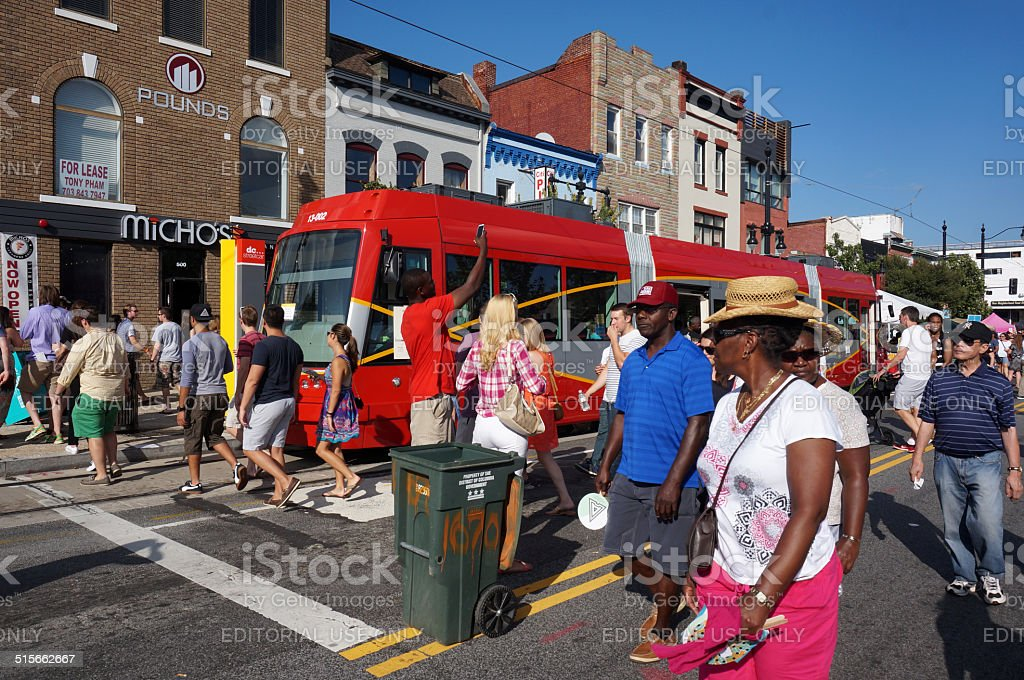 People and Trolley Car Washington DC, USA-September 20, 2014:  These people are walking by and looking at the new trolley car for the District of Columbia at the H Street Festival in downtown Washington DC.  The H Street Festival is an annual event the third week of september featuring arts, crafts, food and entertainment. Adult Stock Photo