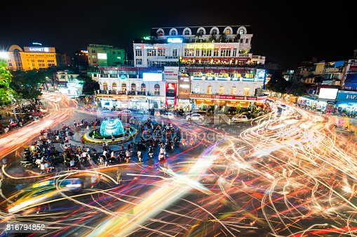 istock People and vehicles light trails crowd on busy intersection locating next to Hoan Kiem lake. 816794852