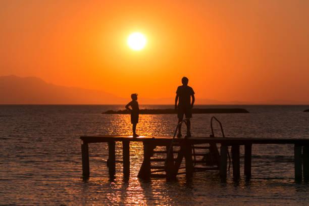Die Menschen sind an der Strandküste von altinova Sommerstadt bei Sonnenuntergang bei ayvalik balikesir Truthahn-Silhouette – Foto