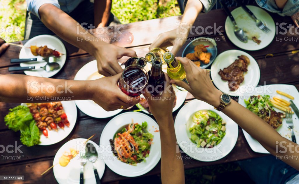 People are eating on vacation. They eat outside the house and clink beer house. stock photo