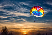 People are gliding with a parachute on the background of sunset.