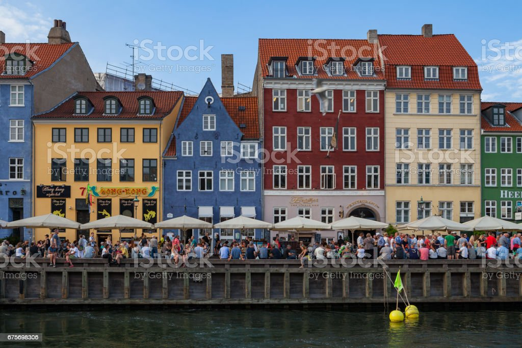 COPENHAGEN, DENMARK - 26 JUNE, 2016: People are relaxing in small canal with colorful houses and boats royalty-free stock photo