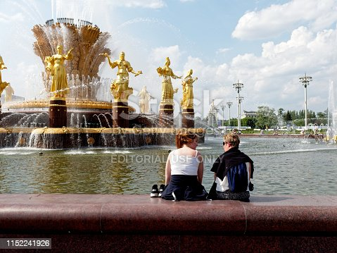Moscow, Russia - May 28, 2019: two young women are resting near the fountain in VDNKh