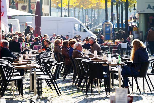 die leute sitzen an den tischen im herbst sunshine - cafe köln stock-fotos und bilder