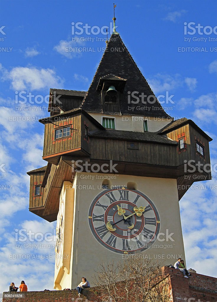 people are sitting nearly city Clock tower in Graz, Austria stock photo
