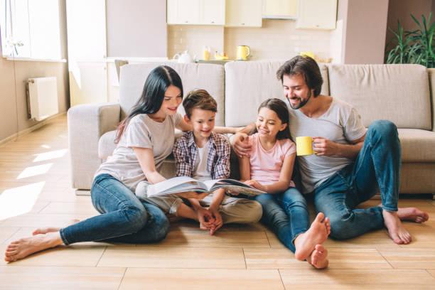 mensen zitten op de vloer. jongen heeft boek. hij leest het met zus en moeder. guy heeft een kopje en kijken naar boek. hij glimlacht. - woman home magazine stockfoto's en -beelden