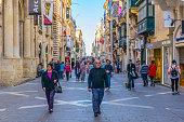 Valetta, Malta, April 30, 2017: People are strolling through a narrow street in the historical center of Valletta, Malta