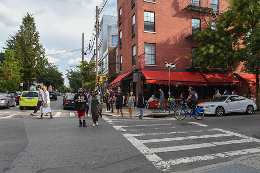 People are walking along Bedford Avenue in Williamsburg