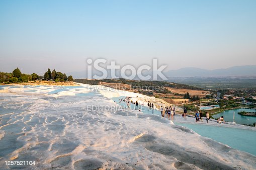 Pamukkale ,Denizli , TURKEY - June 19 2020: People are bathing at thermal Cleopatra's Pool  in Hierapolis in Pamukkale Cotton Castle. Pool is also  called antique pool.There are ancient structures inside pool.So the view of pool is spectacular.Pamukkale is one of the UNESCO World Heritage Site in Turkey.