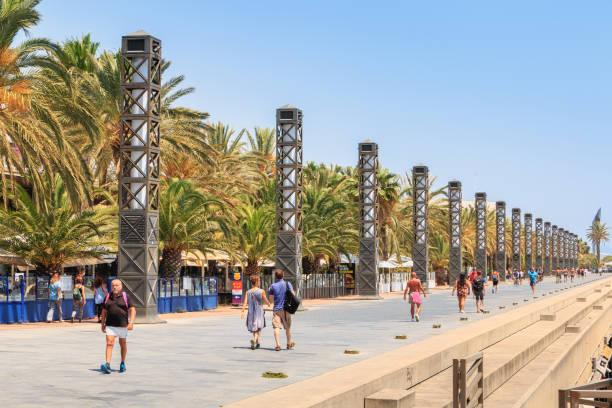 personas están caminando en la playa de barcelona en el final de la jornada - foto de stock