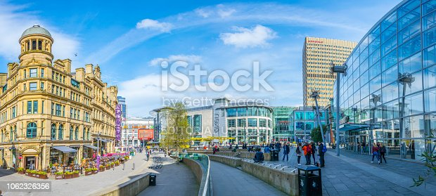 Manchester, UK, April 11, 2017: People are walking on the exchange square in Manchester, England
