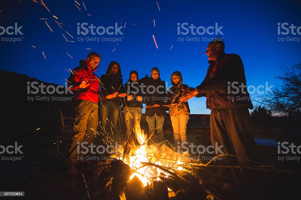 Group of people relaxing near campfire
