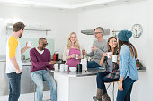 Happy group of people at a creative office taking a break and drinking a cup of coffee in the kitchen