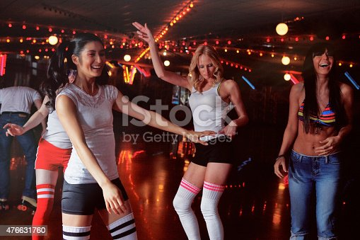 Group of friends having fun at a retro 70's roller disco.