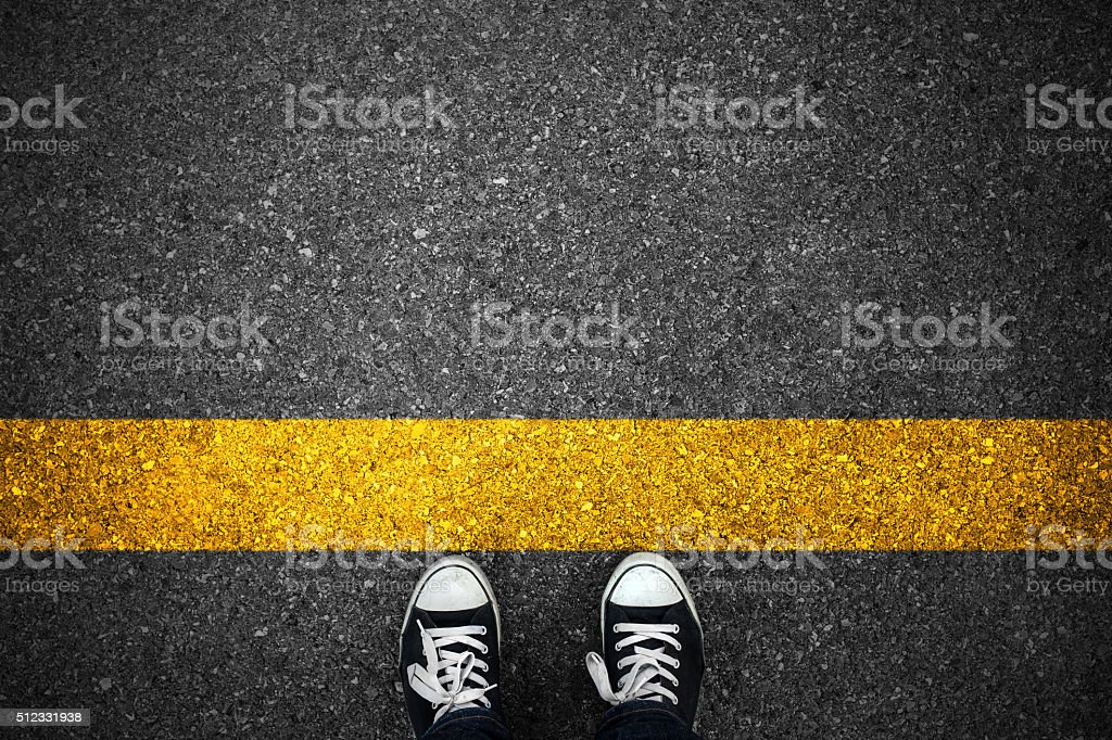 People at a starting yellow line on asphalt stock photo