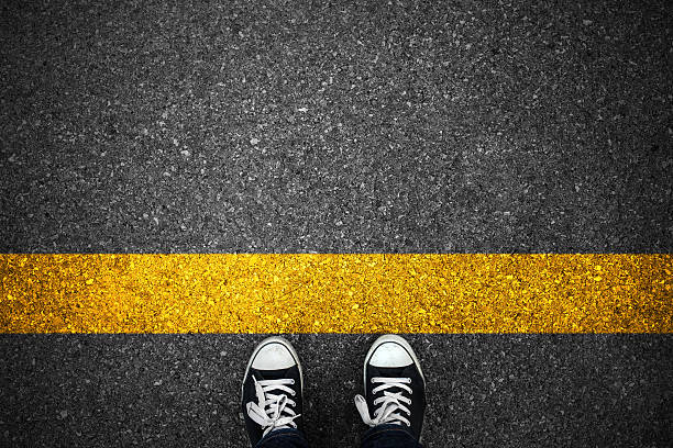 people at a starting yellow line on asphalt - beginnings stock photos and pictures