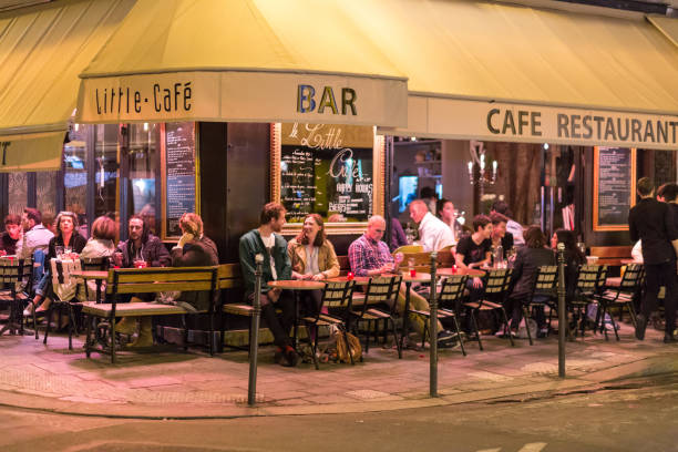 People at a street restaurant at night in Paris stock photo