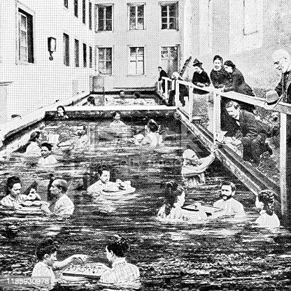 Large group of people at a thermal bath in the town of Leukerbad in Valais Canton, Switzerland. Vintage halftone photo circa late 19th century.