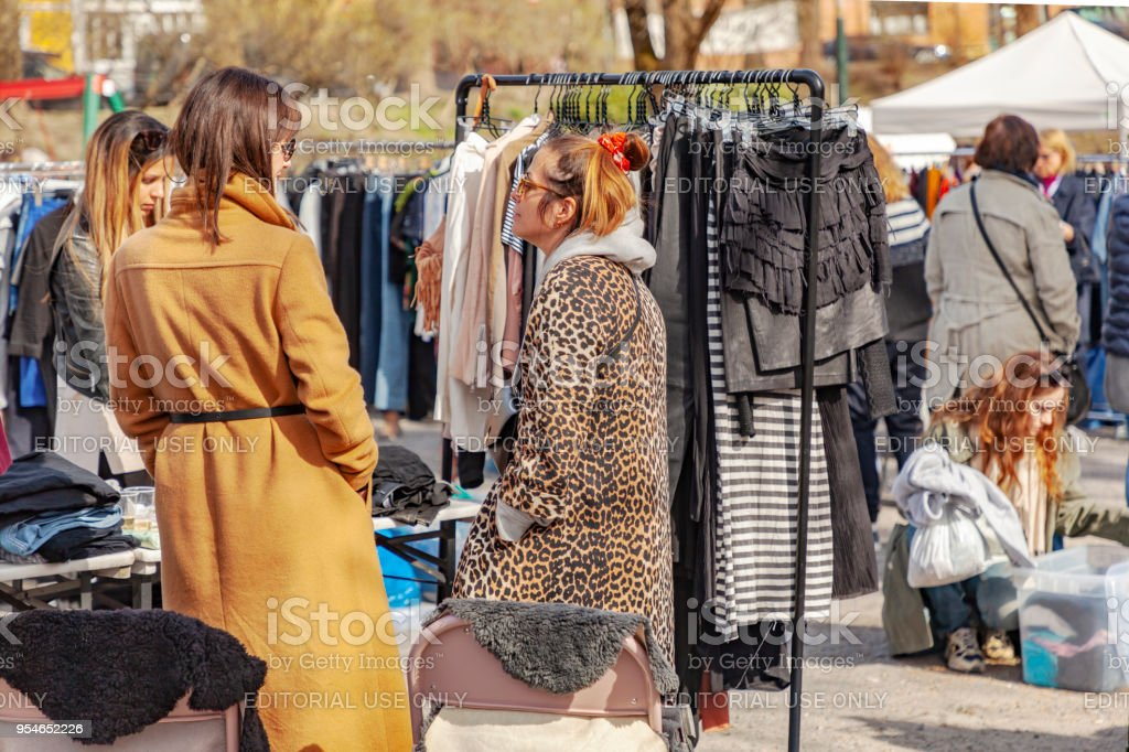 Waomen at an outdoor market looking at second hand clothes. The...