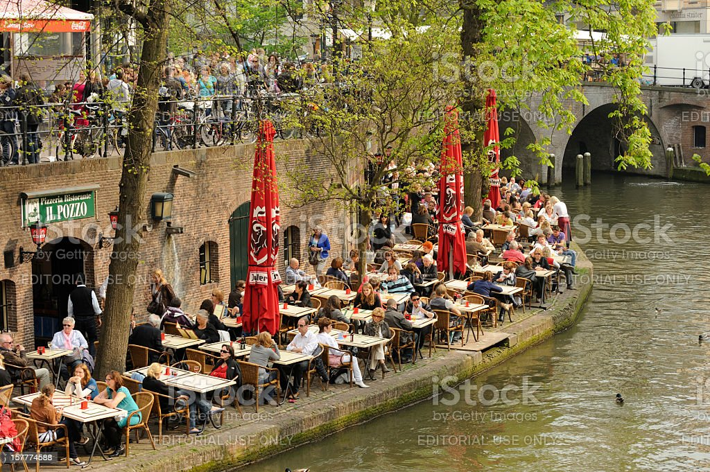 People at an outdoor restaurant on the wharf along Oudegracht stock photo